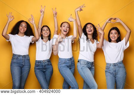 Group Of Multiracial Ladies Gesturing Different Positive Signs And Symbols Raising Hands Posing Over