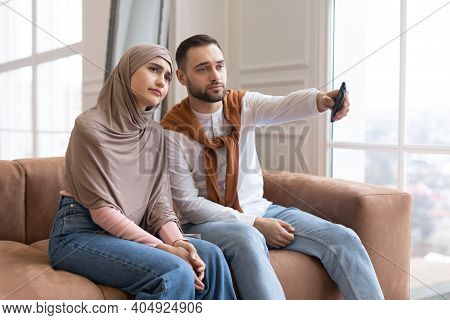 Bored Young Muslim Couple Watching Television Switching Tv Channels With Remote Control Sitting Toge