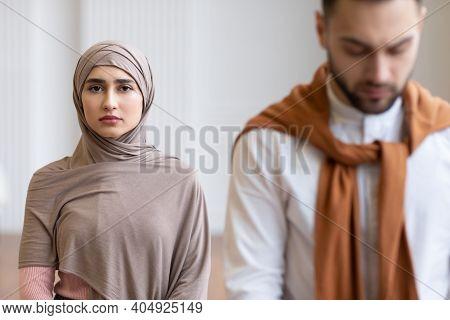 Unhappy Muslim Wife Wearing Hijab Standing Behind Her Husband Looking At Camera Posing Indoors. Fema