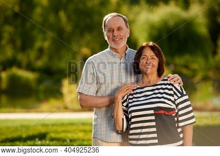 Aged Man And Woman In The Park. Happy Smiling Retired Couple About Fifty Years Old Standing Indoors