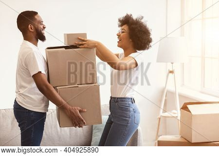Joyful Black Spouses Packing Moving Boxes Together Preparing For Relocation Standing Indoor. Real Es