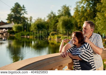 Smiling Mature Couple Enjoying Landscape. Happy Caucasian Man And Woman. Pond And Trees Background.