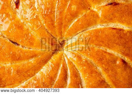 Detail shot of Epiphany cake or galette des rois in French shows the shiny texture of the puff pastry