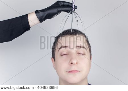 A Man Is Given A Head Massage With A Capillary Massager In The Salon. The Client's Face Shows Relaxa