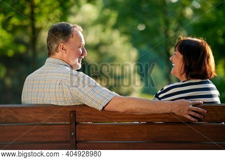 Happy Laughing Couple On The Bench. Mature Retired Man And His Wife In The Park. Loving Couple Looki