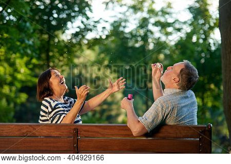 Happy Mature Couple Blowing Bubbles In The Park. Back View Retired Senior Man Making Soap Bubble Whi