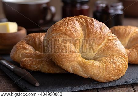 Closeup Of Croissant Pastries On A Slate Board With Butter, Coffee And Preserves In Background