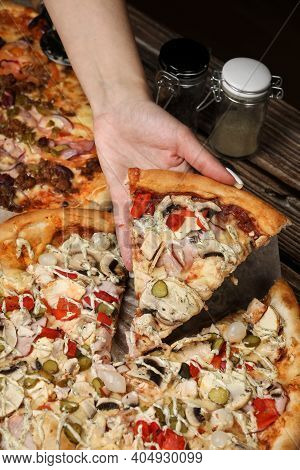 Woman Hand Close Up Holding Pizza Slice On A Wooden Table. Pizza Delivery. Cooking Pizza At Home.