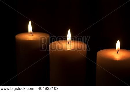 Three Large White Candles Burn In The Dark. Close-up