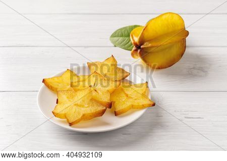 Slises Of Juicy Carambola On A Saucer And One Whole Ripe Star Fruit Over White Wood Table. Ingredien