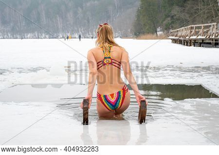 Beautiful Blonde Hair Girl With Colorful Swimsuit Bathing And Swimming In The Cold Water Of A Lake O
