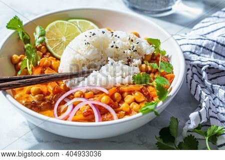 Vegan Chickpea Curry With Rice And Cilantro In A White Bowl, White Marble Background. Indian Cuisine