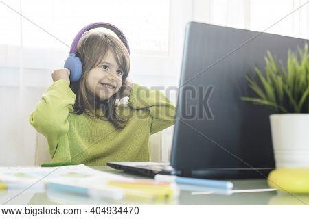 Elementary Schooler Girl In Headphones Sitting At Desk On Laptop - Smiling Cute Girl Studying Online