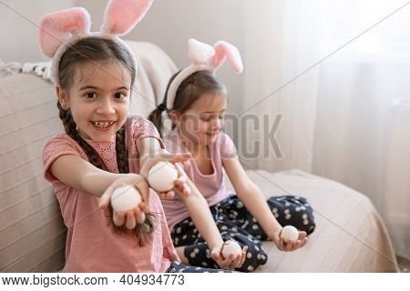 Little Sisters With Bunny Ears And Easter Eggs Posing For The Camera On The Couch At Home. Easter Ph
