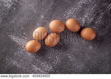 Chicken Eggs On The Background Of A Shabby Wall. Yellow Rustic Eggs On Gray Background