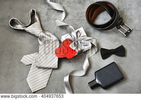 Happy Father's Day. Belt, Bow Tie, Cologne, Belt, Gift Box With A Hearts On A Gray Concrete Backgrou