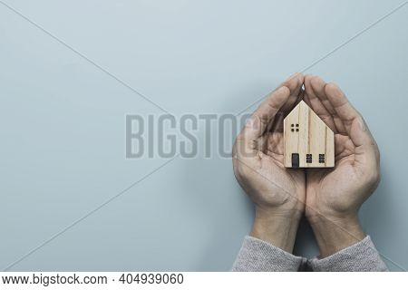 Businessman Holding Wooden House Model On Blue Background , Protect House And Asset Concept.