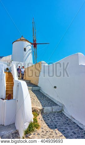 Oia, Santorini, Greece - April 24, 2018: Traditional white windmill in Oia and walking chinese tourists in Santorini