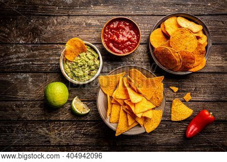 Two Biowls Of Yellow Corn Tortilla Nachos Chips With Salsa And Guacamole Sauce Over Wooden Backgroun