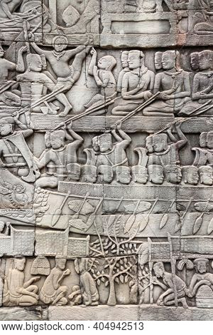 Bas-relief on stone wall of Prasat Bayon temple. Carvings of people in boats and in garden, Angkor Wat (Angkor Thom), Siem reap, Cambodia, Indochina. UNESCO world heritage Site