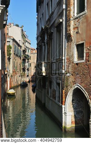 Venice, Italy. Canal, Facades And Boats. Tourists From All The World Enjoy The Historical City Of Ve