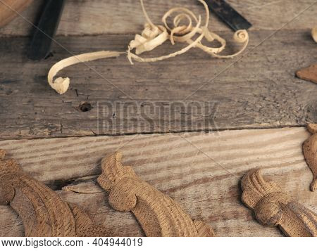 Carved Oak Decorative Elements On A Rustic Workbench With Chisels, Text Free Space In The Center, Wo