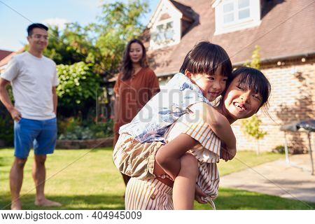 Asian Family Having Fun In Summer Garden At Home With Children Giving Piggyback Rides To Each Other