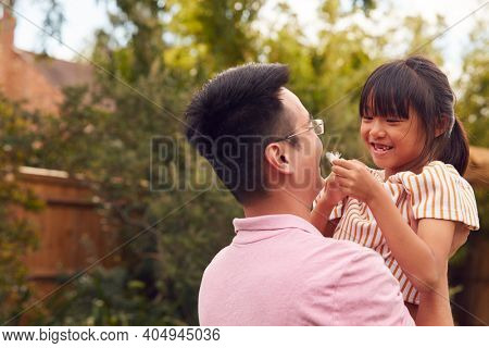 Asian Father Lifting Daughter In Mid Air As They Play Game In Garden Together