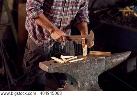 Close Up Of Male Blacksmith Chopping Wood For Kindling On Anvil To Light Forge