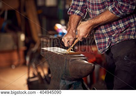 Close Up Of Male Blacksmith Making Wood Shavings With Knife For Kindling On Anvil To Light Forge