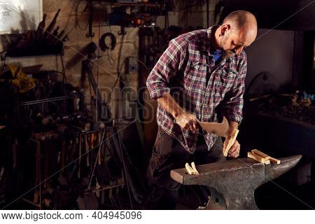 Male Blacksmith Chopping Wood For Kindling On Anvil To Light Forge