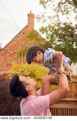 Asian Father Lifting Son In Mid Air As They Play Game In Garden Together