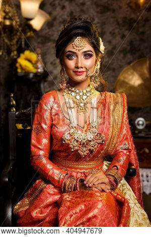 Magnificent Young Indian Bride In Luxurious Bridal Costume With Makeup And Heavy Jewellery Is Sittin