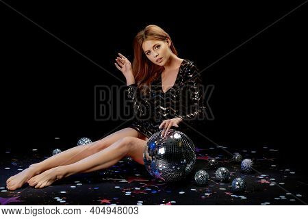 Glamour Model Posing On The Floor. Sexy Blonde Woman In A Black Sequins Dress For Party Near Disco B