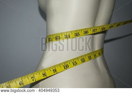 Close Up Of Tape Measure On The Slim Waist Of The Mannequin. The Concept Of A Weight Control Diet An