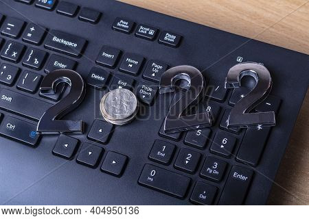 Black Keyboard Close-up. On It Are Laid Out Numbers Of Metal 2022 In The Center Of The Coin 0.25 Dal