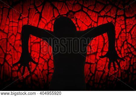 A Black Silhouette Of An Evil And Scary Witch With Outstretched Fingers On A Red Glowing Background.