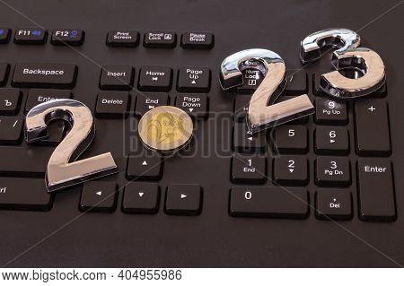 Black Keyboard. Close-up. On It Are Laid Out Numbers Of Metal 2023 In The Center Of The Coin 2 Euro.