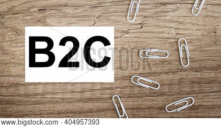 B2c, Text On White Paper Over Wood Background. On Wood Background