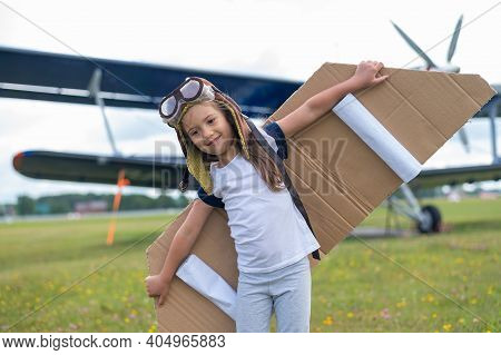 A Little Girl Plays A Pilot On The Background Of A Small Plane With A Propeller. A Child In A Suit W