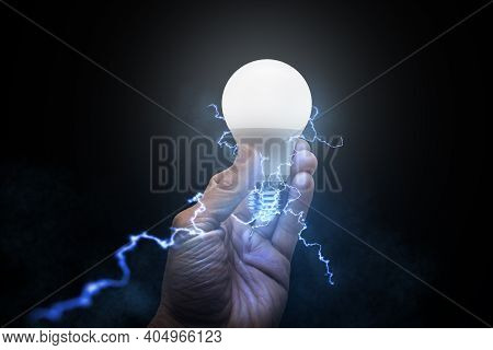 Man Holding Glowing Light Bulb With Electricity And Lightning Bolts Against Black Brackground. Conce