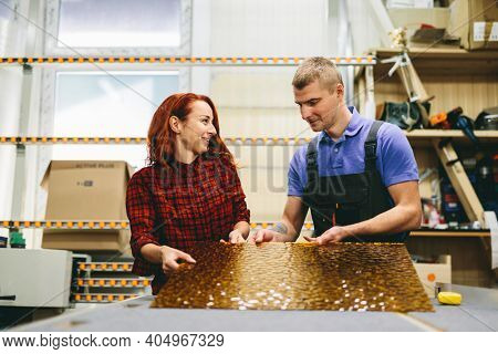 Man and woman working on glass pane in glazier workshop. Industry and manufactory production