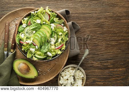 Healthy Green Salad With Avocado And Fresh Cheese On Wooden Table Background