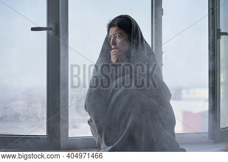 Cold Winter Weather. A Woman Is Shaking From The Cold Sitting On The Windowsill, Wrapped In A Blanke