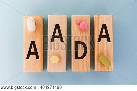 Aada Abbreviation On Cubes With Pill On A Blue Background. Close Aada- Abbreviated Antibiotic Drug A
