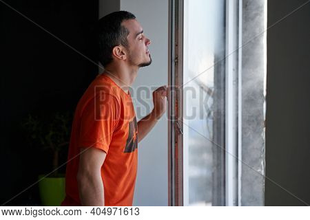 Cold Winter Weather. Man Step To Window, Open It And Frosty Air Rushes From Outside Through Open Win