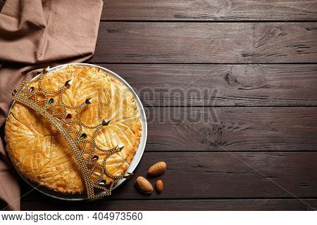Traditional Galette Des Rois With Decorative Crown On Wooden Table, Flat Lay. Space For Text