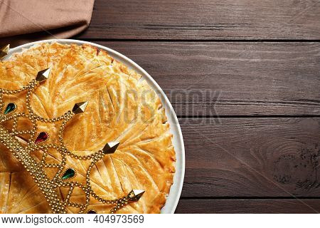 Traditional Galette Des Rois With Decorative Crown On Wooden Table, Top View. Space For Text
