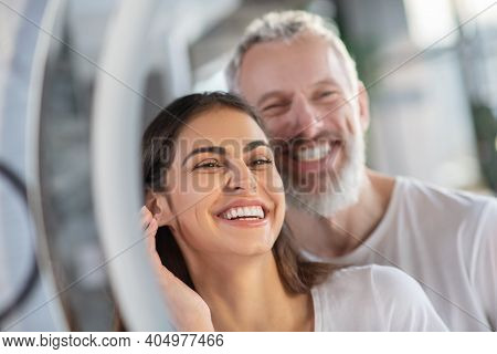 Smiling Woman And Man Looking At The Mirror