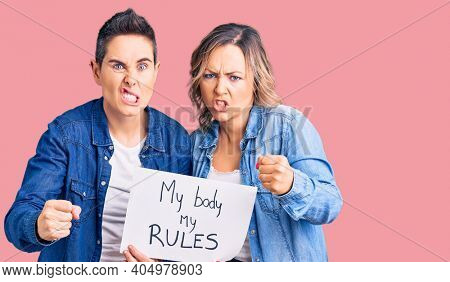 Couple of women holding my body my rules banner annoyed and frustrated shouting with anger, yelling crazy with anger and hand raised